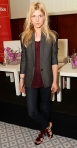Clemence Poesy in a gray blazer, burgundy blouse, dark denim jeans, & flowered flats