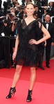 Karolina Kurkova in a black Chanel mini dress with Jimmy Choo booties, a Chopard ring, & a Chanel clutch