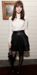 Felicity Jones in a high-neck blouse with a black leather skirt & ankle strap heels