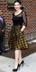 Julianna Margulies in a black sheer top with a houndstooth Carolina Herrera skirt & patent leather heels