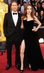 Brad Pitt in a Tom Ford suit & Angelina Jolie in a velvet Atelier Versace gown with Neil Lane jewels, a Jaime Mascaro bag, & custom Salvatore Ferragamo pumpts