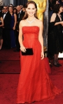 Natalie Portman in a red polk dotted Dior strapless gown with a Charlotte Olumpia clutch