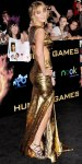 Jennifer Lawrence in a gold lame Prabal Gurung open back gown with a high slit and strappy metallic Jimmy Choo sandals.