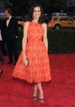 Kristen Wiig in an orange lace 50s inspired gown