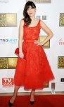 Zooey Deschanel in a red belted Oscar de la Renta tea length dress