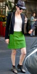 Marion Cotillard in a bright green skirt with a cropped blazer, chain-strap bag, fedora, & studded booties.