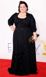 Melissa McCarthy in a black Daniela Kurrle gown with Chopard earrings & a studded Burberry clutch.