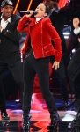 Alicia Keys in a red velvet quilted blazer with black skinny jeans & towering black knee boots.