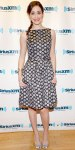 Emmy Rossum in a black printed polka dot dress by Theia with silver satin peep toe pumps.