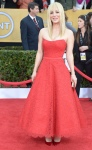 Kaley Cuoco in a red lace overlay sweetheart gown by Romona Keveza with red satin pumps