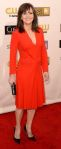 Sally Field in a birght red deep-v long-sleeved dress with a black clutch & black pointed toe heels.