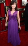 Sally Field in a purple flower & ruched J. Mendel column gown with a black sparkling clutch