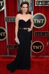 Tina Fey in a black sweetheart belted gown by Oscar de la Renta