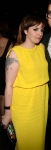 Lena Dunham in a sleeveless yellow blouse dress