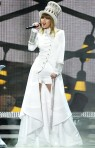 Taylor Swift in a floor-length white jacket with embellished sleeves & white short shorts
