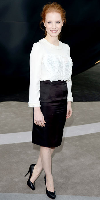 chastain in a white ruffled blouse with a knee