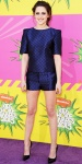 Kristen Stewart in a checkered top & shorts outfits by Osman with black patent Louboutins.