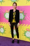 Kristen Wiig in a graphic tee with a black lazer & cropped skinny pants