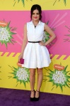 Lucy Hale in a white belted shirt dress by Dior with ankle strap platforms & a pink clutch