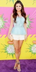 Selena Gomez in a turquoise peplum top by Oscar de la Renta with white shorts, silver sandals by Gucci, & a quilted DVF clutch