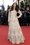 Aishwarya Rai in Abu Jani & Sandeep Khosla white & gold embellished long-sleeved gown with a gold clutch.