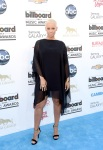 Amber Rose in a black tunic dress with silver & black ankle strap sandals.