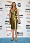 Celine Dion in a gold deep-v cocktail dress with gold pointy toe pumps.
