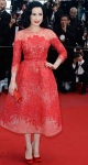 Dita Von Teese in a red lace overlay embellished Elie Saab dress with red satin round toe pumps.