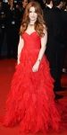 Isla Fisher in a red sweetheart ruched gown by Oscar de la Renta.