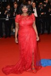 Octavia Spencer in a red lace Tadashi Shoji slitted dress.
