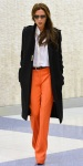 Victoria Beckham in a white button down shirt, orange trousers, a black military jacket, & aviator sunglasses.