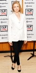 Brit Marling in a white blazer & shirt with black skinny pants & black ballet flats.