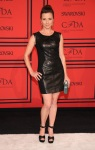 Linda Cardellini in a black leather panel shift dress with black satin ankle strap peep toe sandals.