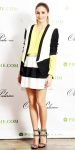 Olivia Palermo in a colorblocked blazer with a matching skirt, bright button-down shirt, & buckled andouble anklestrap sandals.