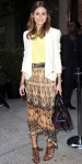 Olivia Palermo in a cream Rebecca Minkoff blazer with a pale yellow top, printed skirt, & a See by Chloe satchel bag.
