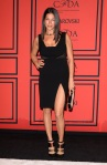 Rebecca Minkoff in a black high-slit dress with multistrap pumps.