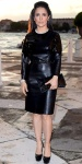 Salma Kayek Pinault in a black leather top & skirt by Bottega Veneta with black round toe platforms, silver & black cuff, & black embossed rectangular clutch.
