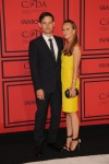 Tobey Maguire & Jennifer Meyer Maguire in a yellow shift dress with black ankle strap sandals.