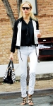 Karolina Kurkova in a black & white outfit with white skinny pants, a zebra bag by Tod's, & black strappy sandals.