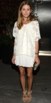 Olivia Palermo in an ivory lace blouse & white pleated skirt with a printed skirt & neutral Aquazurra cut-out booties.