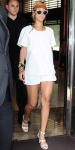 Rihanna in a white tee with white shorts, cat-eye sunglasses, gold jewelry, & strappy studded heels.