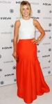 Julianne Hough in a textured white Bec & Bridge top with a floor-length tulip skirt in orange by Halston Heritage, a gold clutch, & gold Jennifer Meyer lizard cuff.