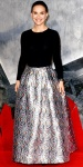 Natalie Portman in a black cashmere sweater with a full silver jacquard skirt by Christian Dior, a black watch, diamond studs, & black Charlotte Olympia pumps.
