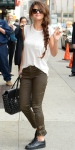 Selena Gomez in a white tee, olive leather buckled pants by Rachel Zoe Collection with oversized shades, gold Melinda Maria hoops, black studded carryall bag, & black sneakers.