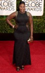 Danielle Brooks in a black brocade & gold sleeveless gown.