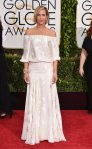 Kristen Wiig in a white off-the-shoulder floral print gown.