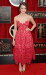 Maisie Williams in a red laser-cut Self-Portrait red tea-length dress with gold pumps.