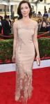 Molly Parker in a blush embellished three-quarter sleeve Lorena Sarbu gown.