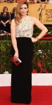 Natasha Lyonne in a gold embellished & black column gown by Proenza Schouler with a gold square minaudiere.