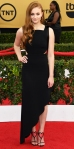 Sophie Turner in a black asymmetric Osman dress, Christian Louboutin heart t-strap shoes, & Vicki Sarge earrings.